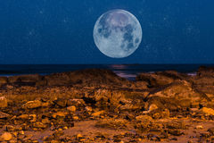 Moon Struck. A night shot of a beach, with an abstract moon and stars Royalty Free Stock Photography