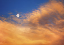 Moon At Sunrise A. Beautiful yellow and orange sunrise clouds with full moon Royalty Free Stock Images