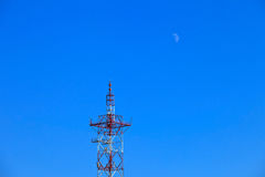 The moon and the TV tower on a clear blue sky day Royalty Free Stock Photo