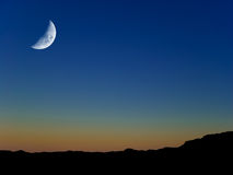 Moon at Twilight. First Quarter Moon at twilight, over clear blue sky Stock Photography