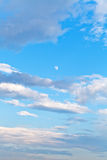 Moon and white clouds in blue evening sky Royalty Free Stock Photo