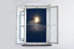 The moon at the window. The moon at night, looking out open white window royalty free stock images