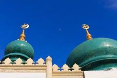 Moon zwischen Oberseite der mit Ziegeln gedeckten Haube der Moschee lizenzfreies stockfoto