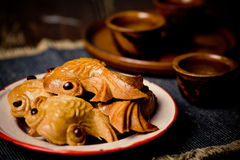 Mooncake cookies. Rustic mooncake cookies on an enamel saucer against dark backdrop royalty free stock photo
