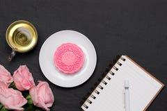 Mooncake da pele da neve e copo de chá com as flores no fundo escuro Imagens de Stock Royalty Free