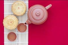 Mooncake mit Tee auf rotem Hintergrund Stockfoto
