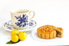 Mooncake tradicional com enchimento da mistura cinco e o copo de chá nuts Foto de Stock