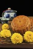 Mooncakes och tea som dekoreras med chrysanthemumen Royaltyfri Foto