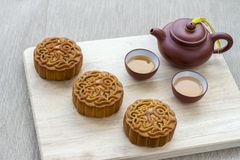 Mooncakes offering to friends or family gathering during the mid-autumn festival. Traditional mooncakes on table setting with tea pot and teacup. The Chinese stock images