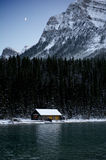 Moonerise behind a lakeside cabin. The moon rises behind a wooden cabin on a lake in the mountains Royalty Free Stock Photography