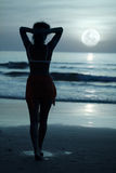 Moonlight. Woman on the beach under moonlight at night time royalty free stock photography