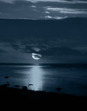 Moonlight. Reflecting on peaceful beach royalty free stock photo