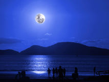 Moonlight on the beach. People on the beach celebrating the moonlight at night royalty free stock image