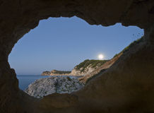 Moonlight through a cave. Seascape of a beautiful beach seen through the hole of a cave, with the full moon shining over the mountains Stock Image