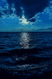 Moonlight in clouds over dark water Royalty Free Stock Images