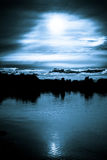 Moonlight in the clouds over a lake Stock Photo