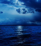 Moonlight in clouds over water Stock Photo