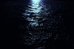Moonlight on dark sea. Moonlight shines on dark sea water. Night sceen at the sea Royalty Free Stock Photos