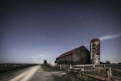 Moonlight farm. Scenic nighttime image of an old farm barn and a country road in moonlight royalty free stock photo
