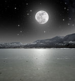 Moonlight on the iced lake. Many stones have been launched on the ice of the lake illuminated by the moonlight stock image