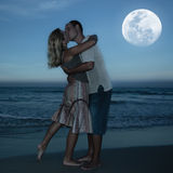 Moonlight kiss. Young couple kissing at the beach under moonlight royalty free stock images