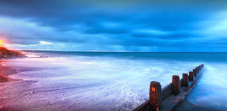 Moonlight lit beach landscape. Moonlight and street lights provide contrasting colors here in this beautiful beach landscape in Tywyn, Wales royalty free stock image