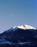 Moonlight and mountain. Sun is shinning on the mountain when the moon appear Stock Photo