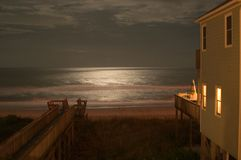 Moonlight on the Ocean. Moonlight reflects off the ocean at Emerald Isle, Nort Carolina. A beachouse is lit on the right and a boardwalk extends from the lower stock photos