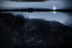 Moonlight over a lake stock images