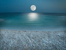 Moonlight on the pebble beach. Pebble beach in the the night wit clear sky with stars, lit by the full Moon just above horizon Royalty Free Stock Photography