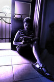 Moonlight reading. A young woman sat on a floor, reading close to a window under the moonlight royalty free stock images