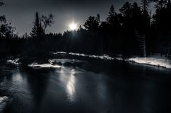Moonlight Reflection over Winter River Snow on Banks stock image