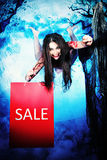 Moonlight sale. Funny witch flying at the night cemetery in the mist and moonlight with shopping bag stock photography