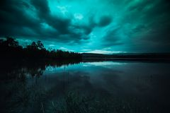 Moonlight shines behind a cloudy at night over tranquil lake. Green tone beautiful natural scenery and night sky stock photos