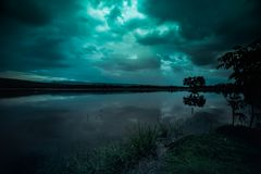 Moonlight shines behind a cloudy at night over tranquil lake. Green tone beautiful natural scenery and night sky royalty free stock image