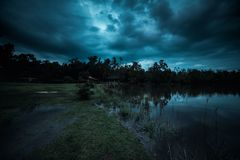 Moonlight shines behind a cloudy at night over tranquil lake. Blue tone beautiful natural scenery and night sky royalty free stock photo