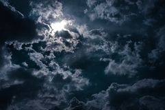 Moonlight shines behind a cloudy at night. serenity background. Moonlight shines behind a cloudy at night. serenity nature background royalty free stock photography