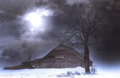 Moonlight and a spooky old barn by the tree Stock Image