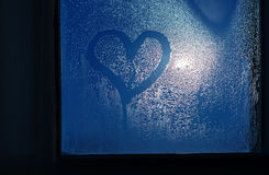 Moonlight through the window. Sweaty glass and heart Royalty Free Stock Photo