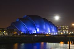 Moonlit armadillo. A full Moon rises over Glasgow's Armadillo building royalty free stock photo