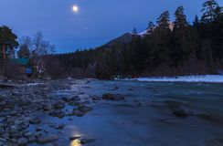 Moonlit night over a mountain river. Nature stock photography