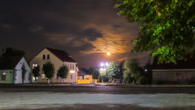 Moonlit night. On the square in the middle of the village. The light of the windows of buildings, the green tree, the clouds and the moon in the sky royalty free stock images