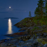 Moonlit night at stony shore of Ladoga lake. Russia stock images