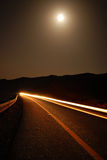 A moonlit road with car trails. A moonlit road in a remote location late at night with car trails royalty free stock photos