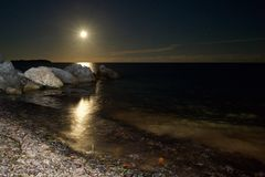 Moonrise över havet vaggar arkivfoton