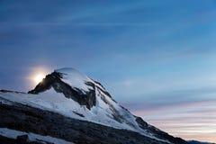 Moonrise über geschneitem Berg Stockfoto