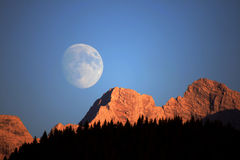 Moonrise. In the Alps with reddish glow of sunlight on the summits of mountains in the foreground stock photography