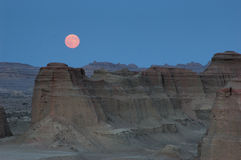 Moonrise. The moon rises on the Urho Ghost Castle immediately after the sun sets. Located at the northwest edge of Zhungarian Basin in Xinjiang and 100 royalty free stock images