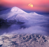 Moonrise among alpine peaks Stock Image