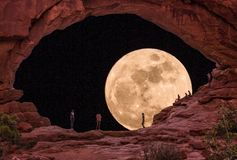 Moonrise at Arches National Park. Nature lovers watching the moonrise through South Window Arch at Arches National Park stock photography
